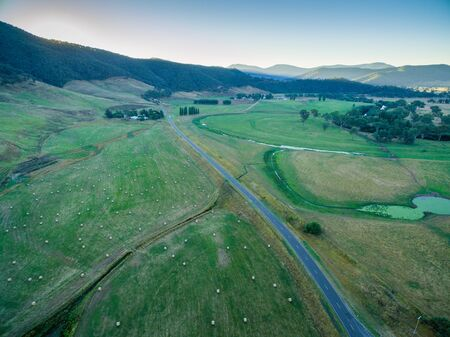 Aerial view of road through Australian backcountry at sunset