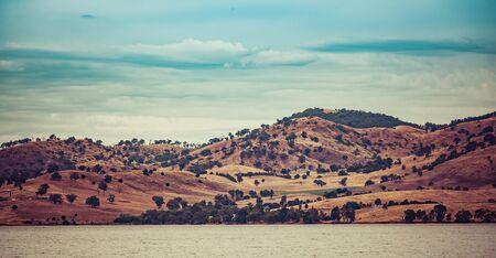 ヒューム湖、ビクトリア、オーストラリアのほとりのなだらかな丘。美しい田園風景の景観