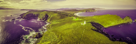 Surreal aerial landscape of ocean, land, and lighthouse in vivid green and purple colors Stock Photo