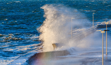 Great wave crushing on Mornington Pier and breakwater creating a rainbow. Melbourne, Victoria, Australia.