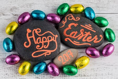 Happy Easter 2017 lettering written on pebbles with chocolate eggs wrapped in colorful foil on white wood background Stock Photo