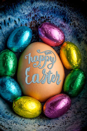 Happy Easter 2017 lettering on egg lined with small chocolate eggs wrapped in colorful foil. Vertical image Stock Photo