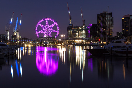 Melbourne, Australia - Feb 21 2016: Observation wheel lit in purple in Docklands, Melbourne with reflections in Yarra river. Night scene.