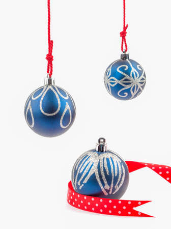 Three hanging Christmas baubles isolated on white.