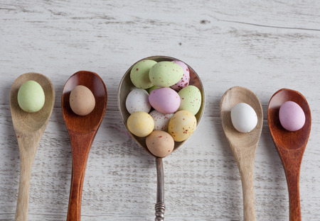 Easter eggs - speckled and sugar coated on wooden and silver spoons on white rustic wooden table, top view Stock Photo