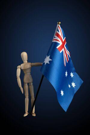 Wooden figurine holding Australian Flag on dark background with blue spotlight Stock Photo