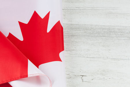 Canadian flag folded creatively on white rustic wooden table. Horizontal image with copy space. Stock Photo