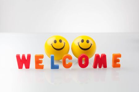 Welcome sign with two smileys on white background.