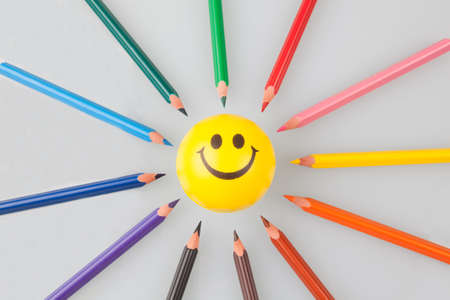 Sharp colorful pencils pointing at smiley face. Stock Photo