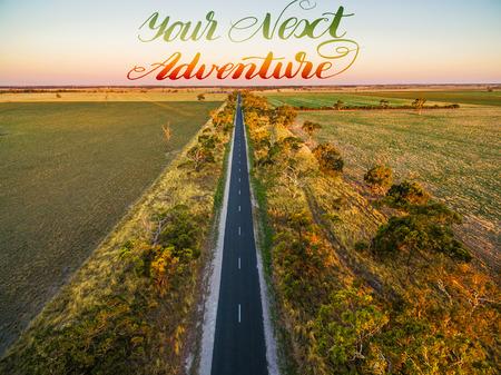 緑の野原と日没 - 手書きのテキスト - あなたの次の冒険の空撮時の牧草地の中で農村地域で長い直線道路 写真素材