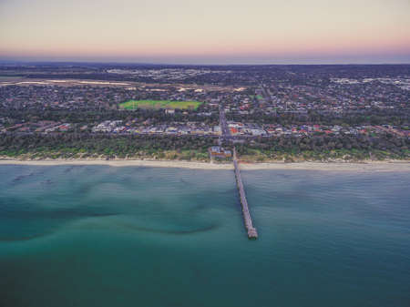 suburbia: Aerial view of Seaford suburb in Melbourne and long wooden pier at dusk