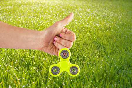 Female hand holding yellow fidget spinner with thumbs up on a grassy sunny background