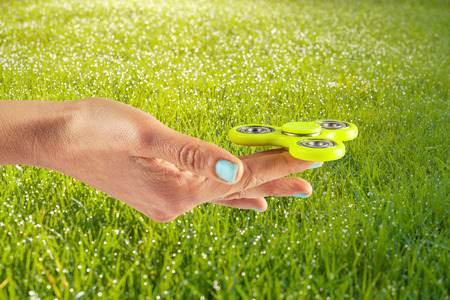 Female hand holding yellow fidget spinner on a grassy sunny background