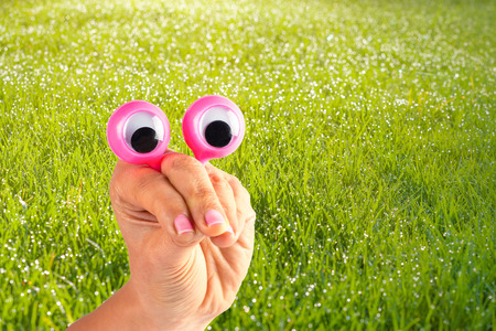 Funny character creature looking very surprised and and trying to intimidate the viewer depicted with female hand and googly eyes on grassy background