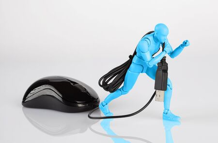 Blue male figurine dragging a computer mouse across white table. Corporate job, slavery, and debt concept with copy space