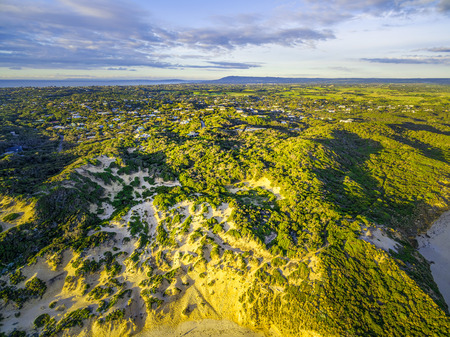 Aerial view of Rye ocean beach coastline with houses scattered in lush vegetation at sunset. Melbourne, Australia Stock Photo