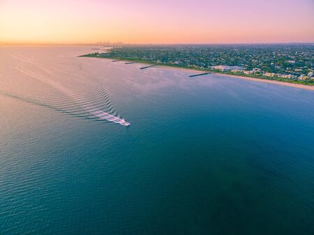 in the suburbs: Aerial view of boat sailing across Port Phillip bay with Melbourne coastline and suburban areas in the background at beautiful sunset