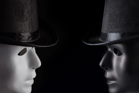 Black and white masks wearing top hats looking at each other isolated on black background with copy space. Dialogue and conversation concept