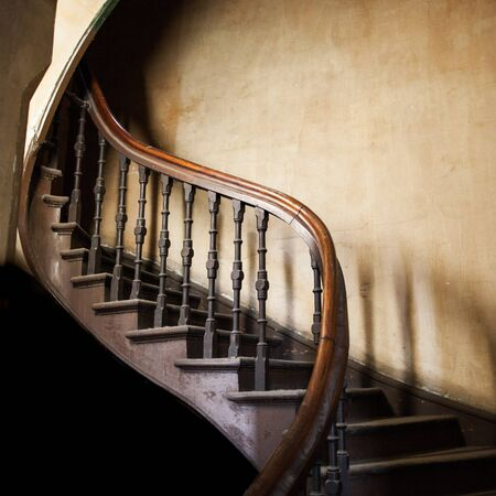Vintage wooden winding staircase going up with copy space on old decaying wall