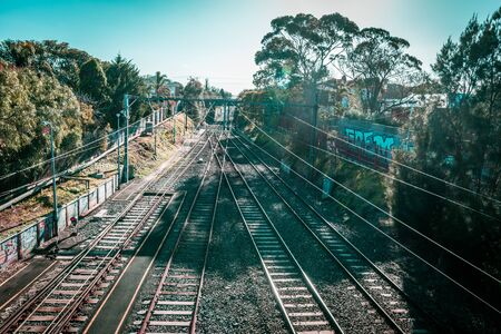 brighton: Melbourne, Australia - July 29, 2017: rail tracks and power lines vanishing in the distance on bright summer day