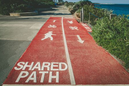 Shared Path sign written on footpath for cyclists and pedestrians with bicycle, walking person, and arrow signs