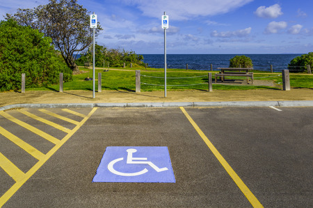 Disabled parking spot and signs in a park near ocean beach