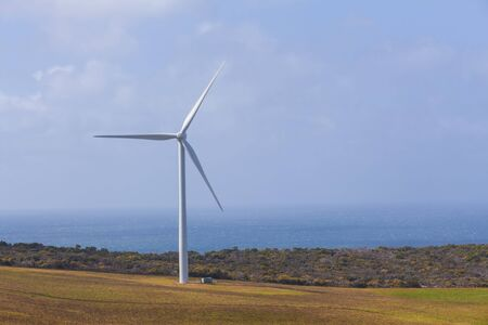 Tall wind turbine standing in a meadow overlooking the ocean