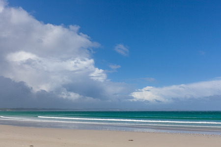 White sand on beautiful ocean beach under stormy clouds and blue sky Stock Photo