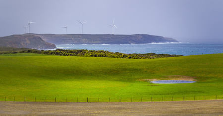 Meadows and pastures with wind turbines standing on a rugged cliff in the background Stock Photo
