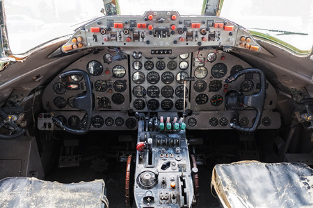 Old aircraft cockpit with steering wheels, control levers, and a lot of gauges