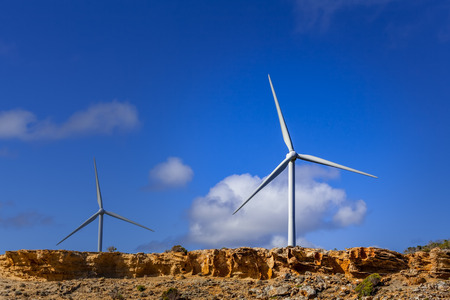 Two wind turbines with vivid blue sky as background and copy space