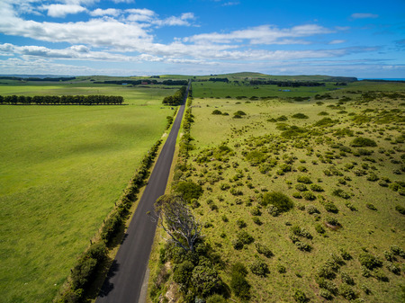 Aerial view of straight road in beautiful Australian countryside on bright summer day