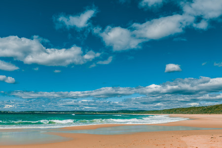 Beautiful ocean beach on bright sunny day with white fluffy clouds landscape