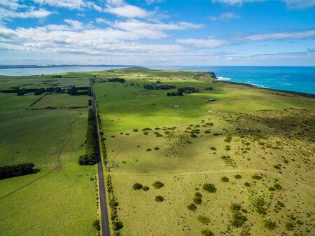 明るい晴れた日に草原や牧草地を通過するまっすぐな農村道路の空中ビュー