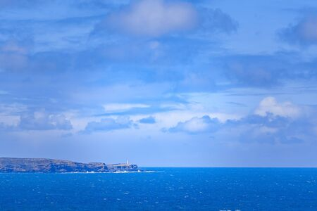 Lighthouse standing on rugged cliff edge overlooking the blue ocean in Australia