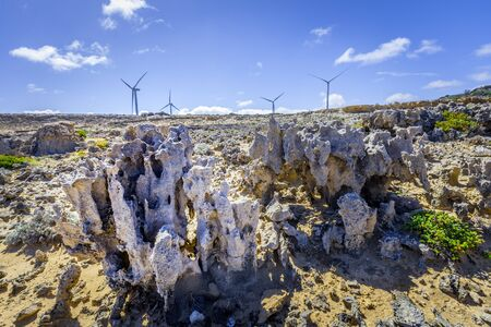 Weathered rock formations and wind turbines - renewable energy and earth conservation concept