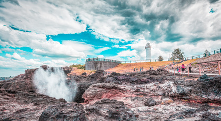 Famous Kiama Lighthouse with water spraying out of the blowhole, Sydney, NSW, Australia