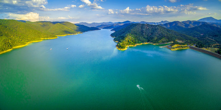 Aerial scenic panorama of beautiful lake and green hills