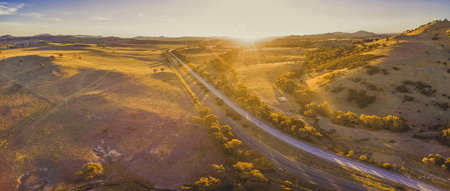 Aerial panorama of Hume Highway passing through scenic countryside at sunset in Australia 写真素材