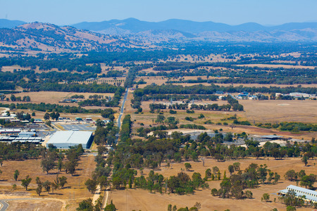 Straight road passing through rural area structures towards mountains in Australia Stock fotó
