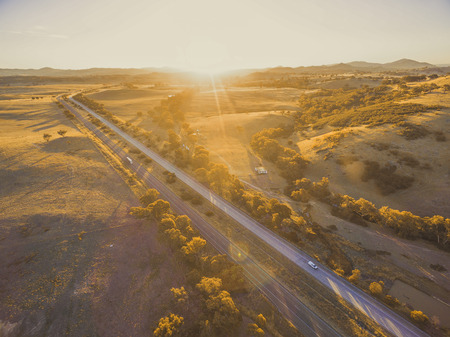 Aerial view of Hume Highway passing through scenic countryside at sunset in Australia 写真素材