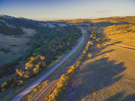 Aerial view of Hume Highway passing through beautiful countryside with long shadows from trees at sunset in Australia