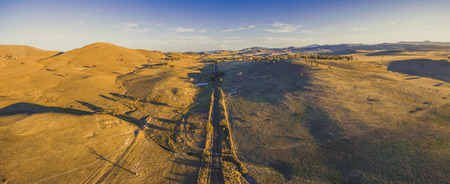 Aerial panorama of straight rural road passing through countryside at sunset 写真素材