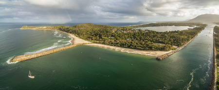 Ocean coastline with boat and rainbow at sunset - beautiful aerial panorama
