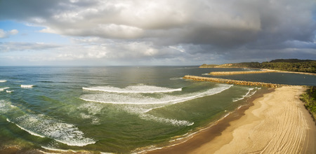 Aerial panorama of stormy sky over ocean coastline at sunset