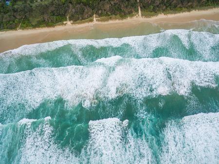 Powerful ocean waves crushing on sandy beach - aerial view Stock Photo