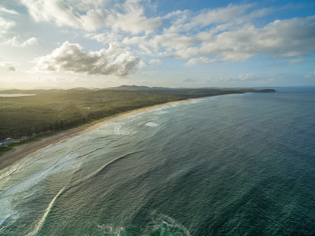 Aerial view of beautiful ocean coastline at sunset
