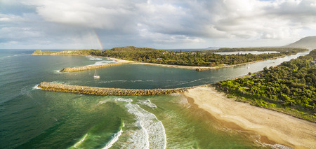 Breathtaking aerial panorama of ocean coastline, rainbow, and boat at sunset Stock Photo