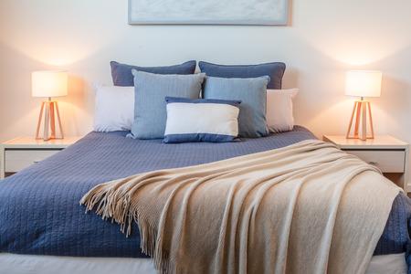 Mooie regeling van kussens op bed in een slaapkamer met bedlampjes en kopie ruimte Stockfoto