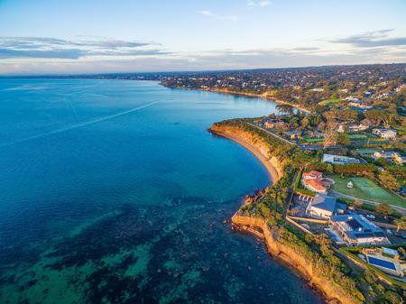 Beautiful rugged coastal cliffs and luxury homes near the ocean - Mornington Peninsula coastline aerial view